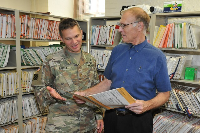 Dr. (Maj.) Frederick Hauser, JMC Command Surgeon, reviews a patient record with Dr. Aaron Jacob, physician at the Rock Island Arsenal clinic.  (Photo credit: Tony Lopez, Joint Munitions Command.)