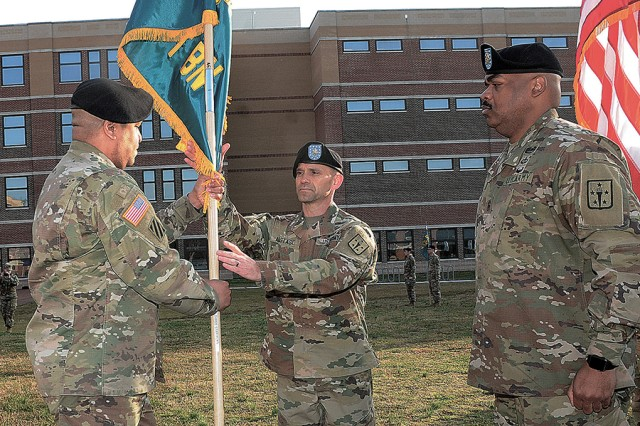 Col. Jamal E. Wigglesworth, Army Logistics University (ALU) commandant, left, passes the newly uncased colors of the ALU Support Battalion to Lt. Col. Matthew K. Anastasi during the 71st Transportation Battalion inactivation ceremony on March 28, 2018. Also pictured is Command Sgt. Maj. Leabarron J. Bates, who helped uncase the colors and serves as the battalion's command sergeant major.