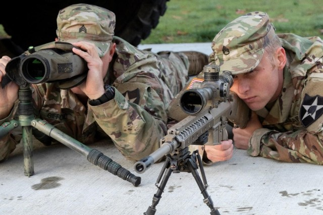 Sgt. Charles Gifford and Staff Sgt. Daniel Grogan, snipers with 1st Battalion, 23rd Infantry Regiment, demonstrate the use of the M110 Sniper Rifle with a spotting scope Oct. 12, at Joint Base Lewis-McChord, Washington. Gifford and Grogan represented 7th Infantry Division during 2018 International Sniper Competition at Fort Benning, Georgia, and placed second among the division teams. (U.S. Army photo by Staff Sgt. Samuel Northrup)