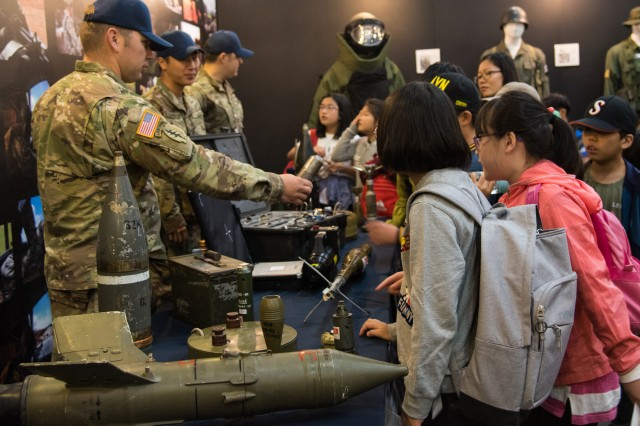 Explosive ordnance disposal specialists assigned to 718th Ordnance Company, 23rd Chemical, Biological, Radiological, Nuclear and Explosive Battalion, 2nd Infantry Division, show the equipment on display to a group of young children at the Eighth Army Experience booth during the Republic of Korea Ground Forces Festival at Gyeryong, South Korea, Oct. 8. The annual, week-long military festival demonstrates ROK and U.S. ground forces capabilities and highlights the continuous partnership between the two nations to festival attendees.