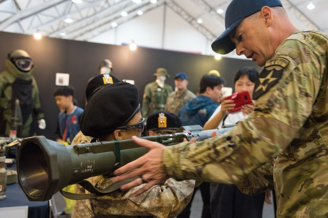 Cpt. Patrick M. Connelly, commander of the 20th Public Affairs Detachment, 2nd Infantry Division, helps a child properly hold an M136 84mm recoilless rifle, or AT4, at the Eighth Army Experience booth during the Republic of Korea Ground Forces Festival at Gyeryong, South Korea, Oct. 5. The annual, week-long military festival demonstrates ROK and U.S. ground forces capabilities and highlights the continuous partnership between the two nations to festival attendees.