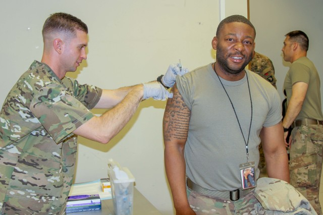 Specialist Phillips Pounders, a US Army combat medic assigned to the 101stResolute Support Sustainment Brigade, inoculates Sgt. Michael Williams, an automated logistics specialist with the influenza vaccine at Bagram Airfield, Afghanistan, Oct. 17.