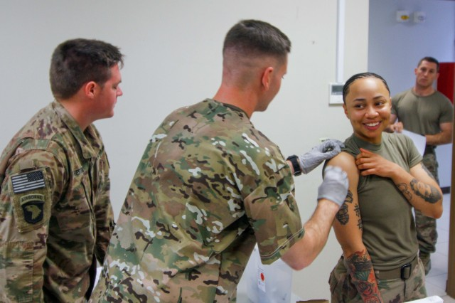 Specialist Phillip Pounders, a combat medic, assigned 101st Resolute Support Sustainment Brigade, inoculates Sgt. Brianna Sherpa, a construction equipment repair specialist, with the influenza vaccine at Bagram Airfield, Afghanistan, Oct. 17.