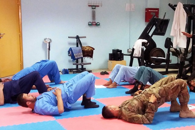 Maj. Nicholas Koreerat (in military uniform), physical therapist for the 1st Security Force Assistance Brigade,  performs a low back class with the director of the 203rd Corps' Physical Therapy Department to actively manage low back pain in the Afghan National Army. (Photo by Staff Sgt. Kyle Harper, 1st SFAB)