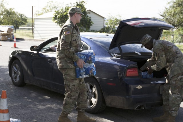 Texas National Guard Pvt Phillip Hiebert,  372nd Combat Support, 36th Sustainment Brigade, sets up a distribution point with local partners, October 2018 at the Kingsland Community Center in Kingsland, Texas. Guardsmen partnered with Salvation Army, American Red Cross, Texas A&M Forest Service and local first responders to give out water, ice and supplies to Texans in need following severe flooding.