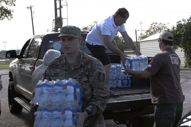 Texas Guardsmen from the 372nd Combat Support, 36th Sustainment Brigade help unload a donation of water from a local citizen at a distribution point in Kingsland, Texas, October 2018 at the Kingsland Community Center. Guardsmen partnered with Salvation Army, American Red Cross, Texas A&M Forest Service and local first responders to give out water, ice and supplies to Texans in need following severe flooding.
