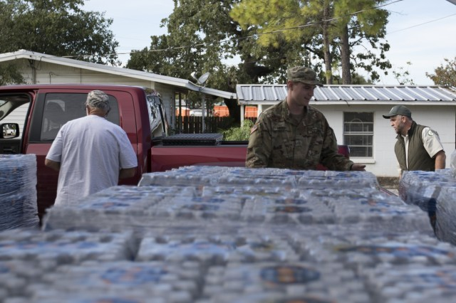 Texas National Guard Pvt Phillip Hiebert,  372nd Combat Support, 36th Sustainment Brigade, hands out water, October 2018 at the Kingsland Community Center in Kingsland, Texas. Guardsmen partnered with Salvation Army, American Red Cross, Texas A&M Forest Service and local first responders to give out water, ice and supplies to Texans in need following severe flooding.