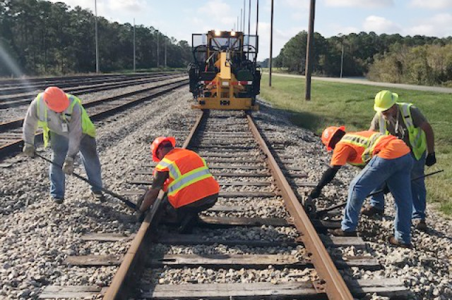 Railroad repairmen work to level out the ballast on track following Hurricane Florence that caused damage to the rail line at Military Ocean Terminal Sunny Point, N.C., on Sept. 26. McAlester Army Ammunition Plant, Okla., deployed a crew of two rail repairmen and three mechanics to help MOTSU reopen its railroad and put two of its inoperable locomotives back into service. MCAAP employees who supported the effort were Jefferson Smith (green vest on right) and Steve Trammell (green vest on left) from the Mobile Off-Site Rail Services team and locomotive mechanics Steve Qualls, Daniel Morrison and Kevin Teague.