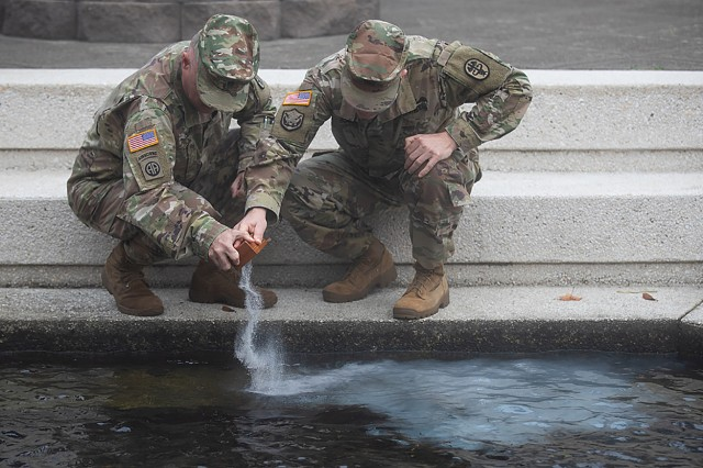 Then Command Sgt. Maj. Mark Bivins and Col. Thomas Bundt, Madigan Army Medical Center's commander and outgoing senior enlisted advisor, commit Madi's ashes to the Madigan Pond at a memorial ceremony for the mute swan that passed away of natural causes at the age of 18. The morning autumn fog offers a peaceful setting for the Oct. 19 ceremony on Joint Base Lewis-McChord, Wash.