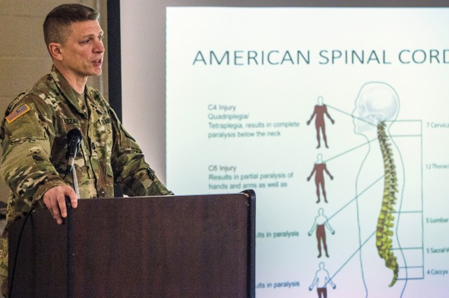 U.S. Army Capt. Domenico Lazzaro, a specialty branch recruiter with the New Jersey Army National Guard, shows the audience a slide of the different levels of spinal cord injuries during the National Disability Employment Awareness Month observance at Joint Force Headquarters located at Joint Base McGuire-Dix-Lakehurst, N.J., Oct. 18, 2018. On June 11, 2017, Lazzaro fell while navigating an obstacle course at Joint Base McGuire-Dix-Lakehurst and fractured his T8 vertebrae. The seven-hour surgery left him paraplegic. Lazzaro's goal is to be able to pass the Army physical fitness test and continue to serve in the Guard.
