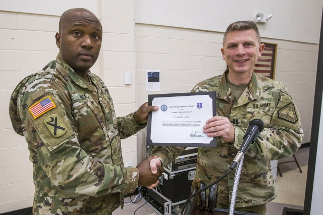 U.S. Army Brig. Gen. Jemal J. Beale, left, the Adjutant General of New Jersey, presents Capt. Domenico Lazzaro, a specialty branch recruiter with the New Jersey Army National Guard, a certificate of appreciation during the National Disability Employment Awareness Month observance at Joint Force Headquarters located at Joint Base McGuire-Dix-Lakehurst, N.J., Oct. 18, 2018. On June 11, 2017, Lazzaro fell while navigating an obstacle course at Joint Base McGuire-Dix-Lakehurst and fractured his T8 vertebrae. The seven-hour surgery left him paraplegic. Lazzaro's goal is to be able to pass the Army physical fitness test and continue to serve in the Guard.
