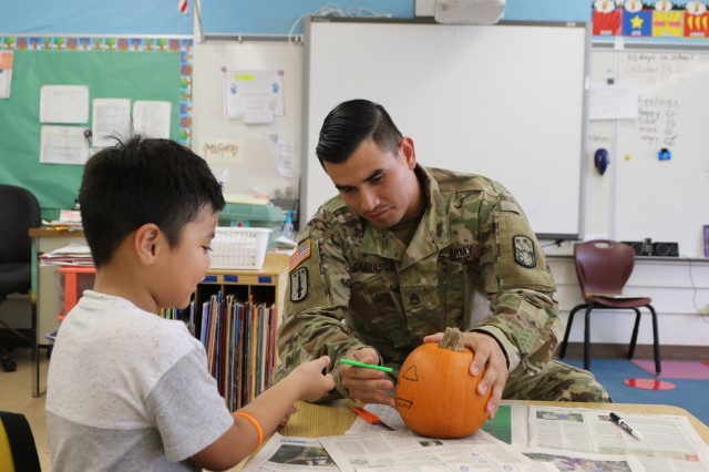 Staff Sgt. Manuel Carrasco carves a pumpkin with a student on October 25, 2018 at Linapuni Elementary School in Honolulu, Hawaii. Soldiers from 94th Army Air and Missile Defense Command participated in this event to give back to the community they are part of.