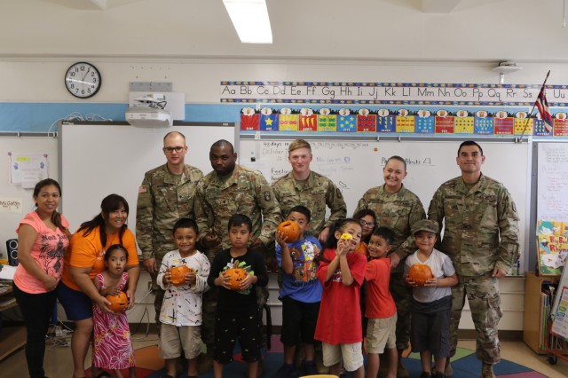 Soldiers from the 94th Army Air and Missile Defense Command smile for a group photo with students and teachers after a pumpkin carving event on October 25, 2018 at Linapuni Elementary School in Honolulu, Hawaii.