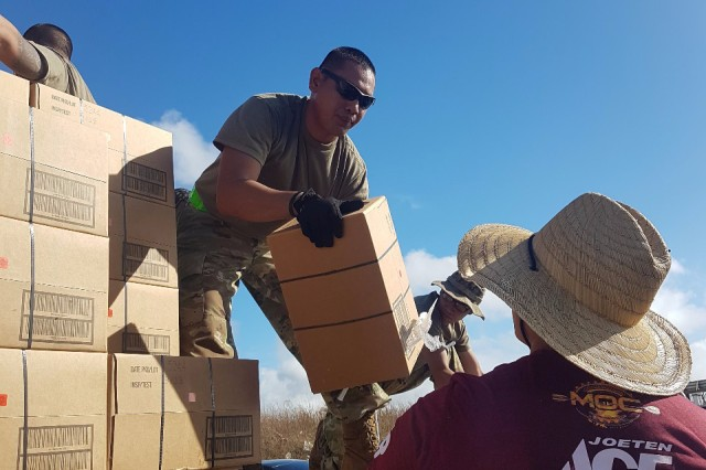 Soldiers with E Company, 100th Battalion, 442nd Infantry Regiment, 9th Mission Support Command, assist local volunteers and government agencies in distributing essential disaster relief supplies at the Ada Gym, Saipan, Oct. 28, 2018 following the destruction left by Super Typhoon Yutu.