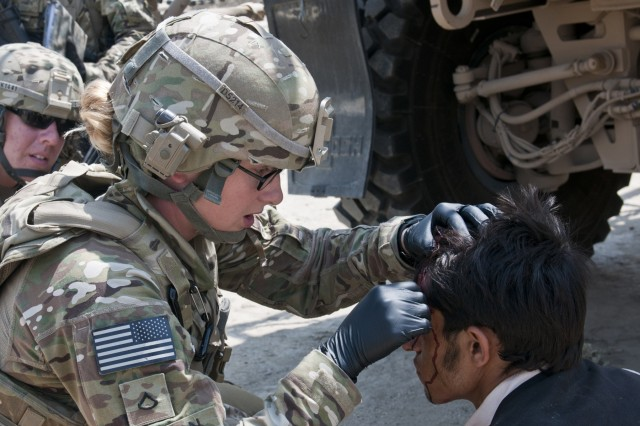 U.S Army Pfc. Rachelle Dutton, the medic with the Military Police squad in Headquarters Headquarters Company, 45th Brigade Special Troops Battalion, examines a patients head wound before treating the wound. Dutton treated as many as six patients who had injuries ranging from minor scrapes to open head wounds.