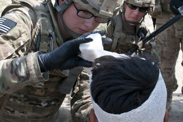 U.S Army Pfc. Rachelle Dutton, the medic with the military police squad in Headquarters Headquarters Company, 45th Brigade Special Troops Battalion, treats an open head wound of an Afghan who was involved in a wreck involving a bus full of people. Dutton treated as many as six patients who had injuries ranging from minor scrapes to open head wounds.