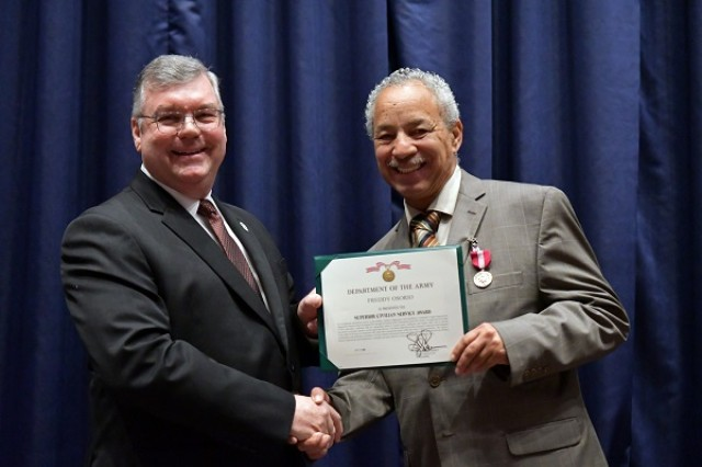Freddy Osorio, Director of Equal Opportunity for the Military Surface Deployment and Distribution Command (SDDC) and Bryan Samson, Deputy to the Commander for SDDC, smile after Osorio is presented the Superior Civilian Service Award during a retirement ceremony in Osorio's honor, Oct. 26, 2018. (U.S. Army photo by Kimberly Spinner)