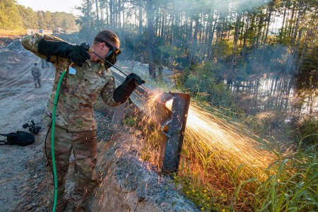 A Soldier with the 57th Sapper Company (Rough Terrain), 27th Engineer Battalion cuts through a guard rail using an exothermic cutting torch. Elements of the 27th Engineer Battalion are assisting the U.S. Army Corps of Engineers in the recovery efforts on the Military Ocean Terminal Sunny Point, N.C., which was damaged by Hurricane Florence. The guard rail was twisted when the road under it was washed out by the storm.