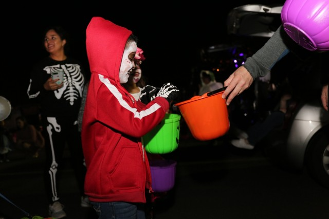 Camp Zama's trick-or-treater receives a candy from U.S. Army Aviation Battalion Japan staff during the haunted hangar and trunk-or-treat event hosted by USAABJ on Oct. 30, 2018, at Camp Zama's hangar.