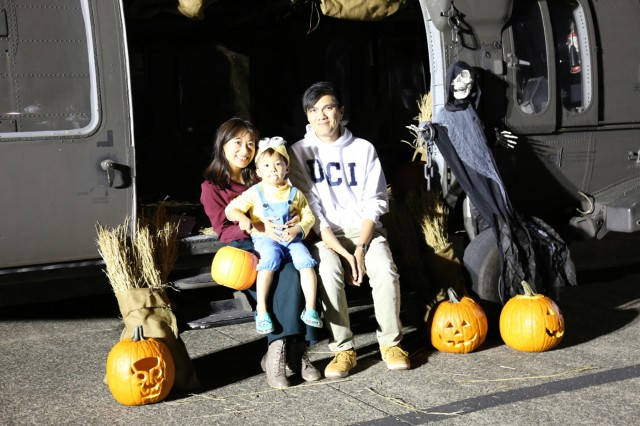 Event participants pose for a photo opportunity by the decorated UH-60 Blackhawk during the haunted hangar and trunk-or-treat event hosted by U.S. Army Aviation Battalion Japan on Oct. 30, 2018, at Camp Zama's hangar.