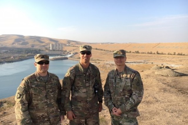 Staff Sgt. David Gills and Capt. James MacGibbon of the 569th Engineer Dive Detachment and Maj. David Kenna, Operations Officer from ASG-Kuwait's Brigade Special Troops Battalion pose for a photo with the Mosul Dam in Mosul, Iraq, Nov. 29, 2017.