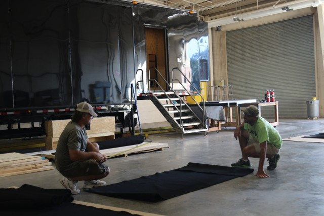 Part of the MSB team that keeps display vehicles running year-round, contractors cut felt panels to line the walls of the Army's new STEM Experience, set to launch in December.