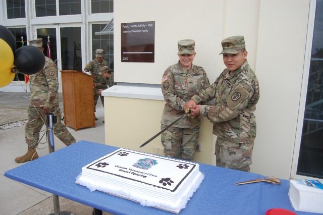 Col. Rebecca Porter, Public Health Command Europe commander, and Sgt. José Armendariz, an animal care sergeant at Vicenza Veterinary Treatment Facility, cut the cake during the grand opening of the new veterinary treatment facility.