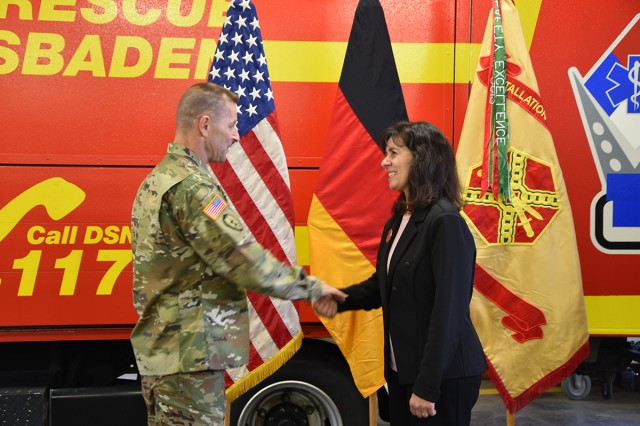 Installation Management Command Commanding General Lt. Gen. Bradley A. Becker presents a coin to Federica LeMauk during a visit to U.S. Army Garrison Wiesbaden Oct. 29.