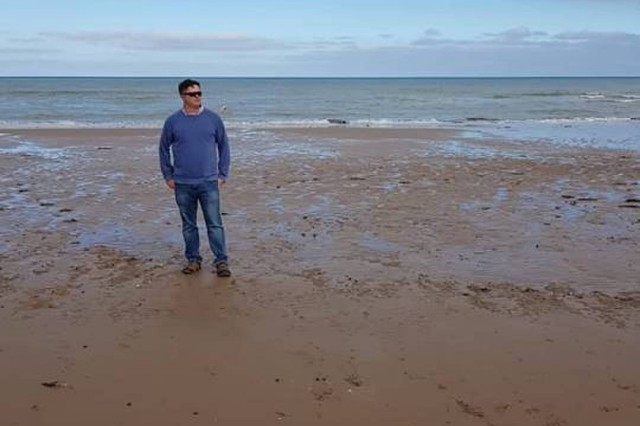 SFC Joshua Fulghum stands in the exact spot where his grandfather, Pfc. Howard Masters, stepped on July 1, 1944, at Omaha Beach. Senior noncommissioned officers were taking part in U.S. Army Europe Command Sgt. Maj Rob Abernethy's staff ride to Normandy, France between Oct. 23-26, 2018.