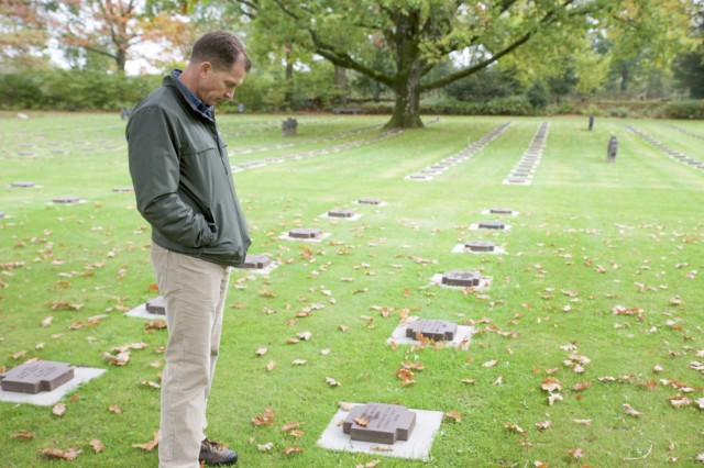 Command Sgt. Maj. Rob Abernethy reads the grave marker of a German soldier who fought during World War II on the last day of the staff ride in Normandy, France. Senior noncommissioned officers were taking part in a U.S. Army Europe staff ride to Normandy, France between Oct. 23-26, 2018.