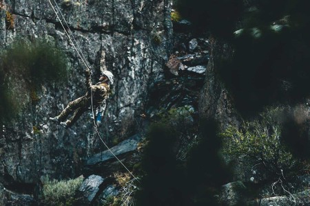 A Special Forces Soldier with Operational Detachment Alpha conducts a tyrolean traverse over an 80-foot gorge, aboard Marine Corps Mountain Warfare Training Center, Bridgeport, Calif., July 23, 2018. Any special operations force element that comes to MCMWTC has the opportunity to do their list of schools; ranging from assault climber, mountain medicine, mountain sniper among others, or they can program their own training through use of an internal mountaineering subject matter expert.