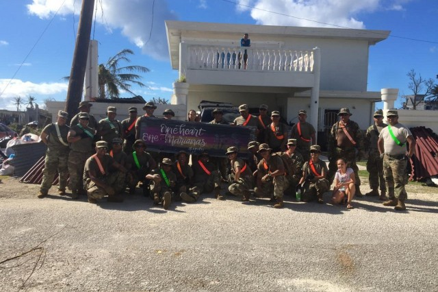 SAIPAN, Commonwealth of the Northern Mariana Islands - Soldiers with the 9th Mission Support Command, U.S. Army Reserve, take a photo with Saipan residents, while holding up a piece of artwork made by debris caused by Super Typhoon Yutu, Oct. 31. The Soldiers, assigned to support the Saipan Mayor's Office, conducted route clearance and debris cleanup. Service members from Joint Region Marianas and Indo-Pacific Command are providing Department of Defense support to the Commonwealth of the Northern Mariana Islands' civil and local officials as part of the FEMA-supported Typhoon Yutu recovery efforts. (Photo courtesy)
