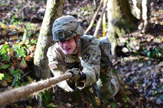 "A cadet with the University of Louisville attempts to negotiate a rope obstacle at ""The Pit of Misery"" during the 2018 7th Brigade Bold Warrior Challenge at Fort Knox, Kentucky, Nov. 3. Eighteen university ROTC teams competed for top honors."