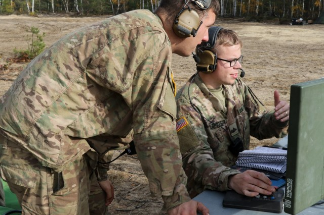 Spc. Zachary Kinder, left, and U.S. Army Pfc. Brigham Albertson, both unmanned aircraft systems operators assigned to Delta Company, 91st Brigade Engineer Battalion, 1st Armored Brigade Combat Team, 1st Cavalry Division, monitor and control the RQ-7B Shadow using a portable ground control system at Horsemen Flight Landing Strip in Trzebien, Poland, Nov. 1, 2018.