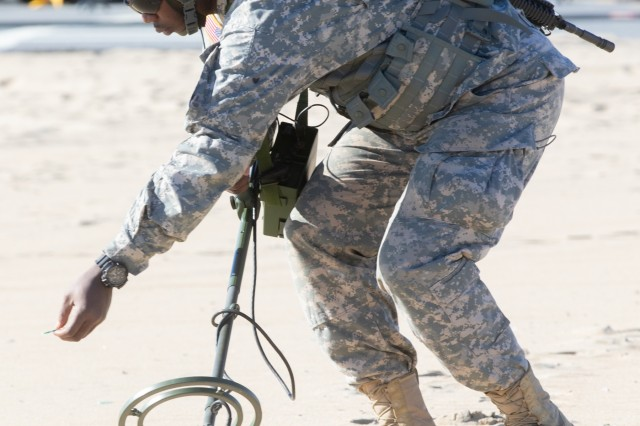 A Soldier from the 253rd Engineer Company, marks an area where a possible simulated mine might be hidden during a domestic emergency response exercise at Ocean City, Maryland on Nov. 3, 2018. Soldiers walk in a straight line, scanning five-feet side to side listening for the signal of a possible ordnance with a metal detector hooked up to a headset the soldier wears.