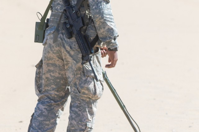 Spc. Daniel Vaughn, 253rd Engineer Company, scans the beach with a metal detector looking for a simulated mine hidden during a domestic emergency response exercise at Ocean City, Maryland on Nov. 3, 2018. Soldiers walk in a straight line, scanning five-feet side to side listening for the signal of a possible ordnance with a metal detector hooked up to a headset the soldier wears.