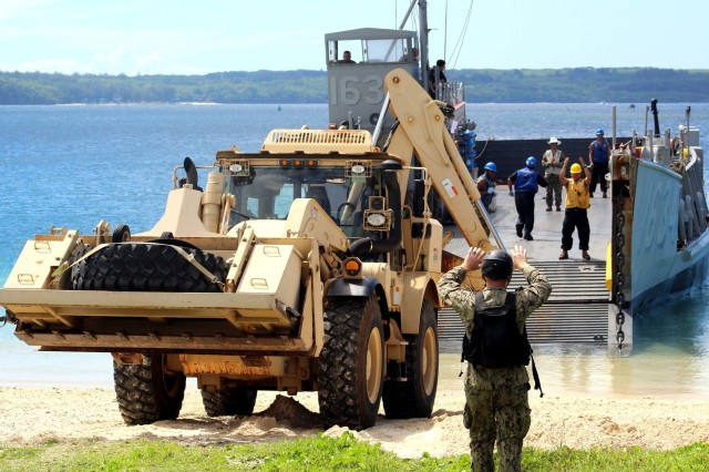 Sailors assigned to Naval Beach Unit (NBU) 7, load a high-mobility excavator from the 1224th Engineering Support Company, Guam Army National Guard, onto Navy Landing Craft, Utility (LCU) 1634 at the Reserve Craft Beach in Guam. NBU-7 and Guam Army National Guard work to together to load 18 heavy equipment vehicles onto the Whidbey-Island class amphibious dock landing ship USS Ashland (LSD 48). Ashland is at Naval Base Guam to transport heavy equipment vehicles to Saipan in support of disaster relief efforts after Super Typhoon Yutu.