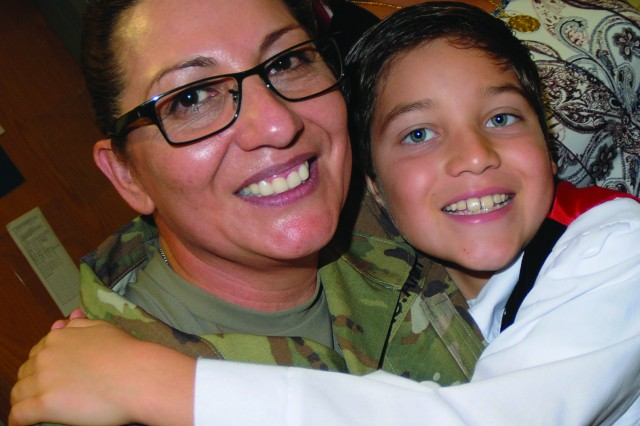 Chief Warrant Officer 5 Maria Martinez, 30 years a Soldier, hugs her son Mauricio Jr., during an assumption of responsibility ceremony Nov. 5. Martinez was named Chief Warrant Officer of the Quartermaster Corps during the event, the first woman to hold the position.