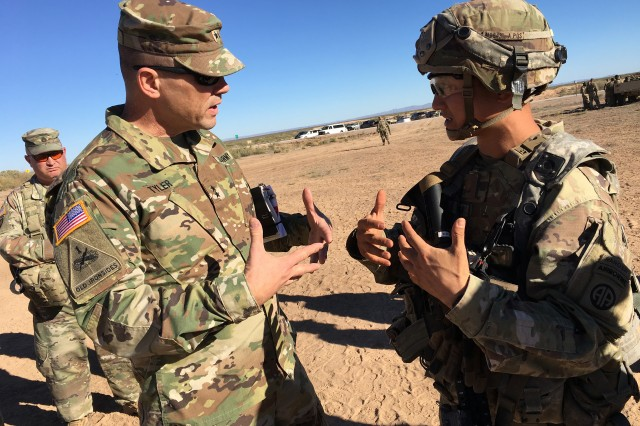 WHITE SANDS MISSILE RANGE, N.M. (Nov. 7, 2018) — Maj. Gen. Joel K. Tyler (left), commander of the Aberdeen Proving Ground, Md.-based U.S. Army Test and Evaluation Command (ATEC), chats with Maj. Shigenobu T. Morinaga, executive officer for 3rd Brigade Combat Team (BCT), 82nd Airborne Division from Fort Bragg, N.C., about how modern battlefield communication systems work together, during the Network Integration Evaluation (NIE) 18.2 at the Digital Multi-Purpose Training Range here. The 3rd BCT is the rotational unit testing the Army's communications backbone during NIE 18.2, which runs through Nov. 12. It is a Soldier-led evaluation exercise designed to integrate and rapidly progress the Army's battlefield communications network. As the ATEC commander, part of Tyler's job is to plan, integrate, and conduct independent operational testing. To that end, independent evaluations like NIE 18.2 provide essential information to Army acquisition decision makers and senior commanders.