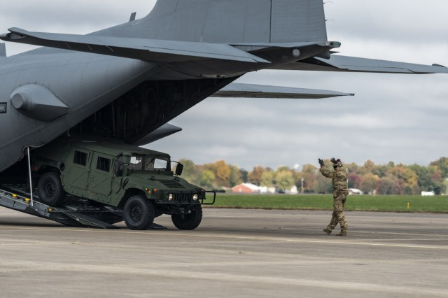 An Airman with the 169th Air Support Operations Squadron directs a vehicle off the ramp of a C-130 Hercules at the Marion Airport in Marion, Illinois, during the Prairie Assurance exercise Nov. 2. The Peoria, Illinois, based 169th ASOS is part of the 182nd Airlift Wing and was one of a handful of units that participated in the tactical communications exercise portion of Prairie Assurance Nov. 2.