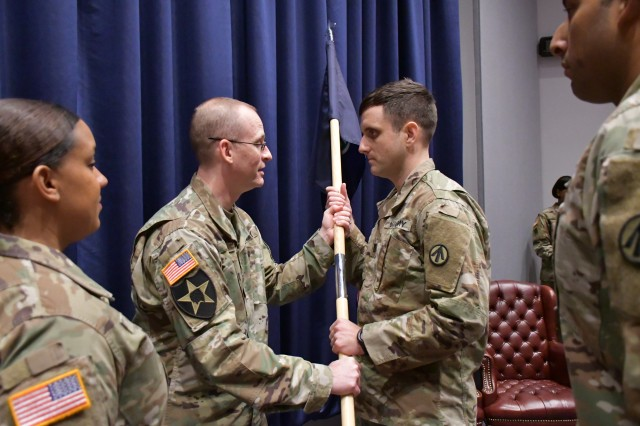 Col. Zorn T. Sliman, Chief of Staff of the Military Surface Deployment and Distribution Command, passes the Headquarters, Headquarters Detachment guidon to Capt. Christopher L. Fetterman during change of command ceremony in the Seay Auditorium at Scott Air Force Base, Ill. Nov. 6, 2018.