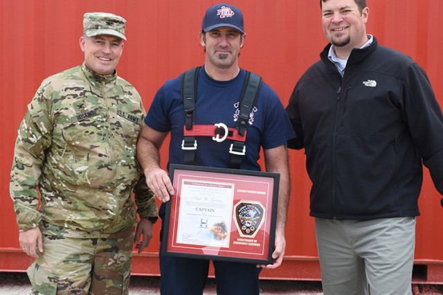 181009-A-BB276-010 The opportunity was taken to recognize Firefighter Paul Greene with a plaque, noting his promotion to captain, Oct. 9, 2018 during Firefighter Skills Day at Dugway Proving Ground, Utah. At left: Col. Brant Hoskins, commander of Dugway Proving Ground. Right: Garrison Manager Aaron Goodman. Photo by Al Vogel, Dugway Proving Ground Public Affairs