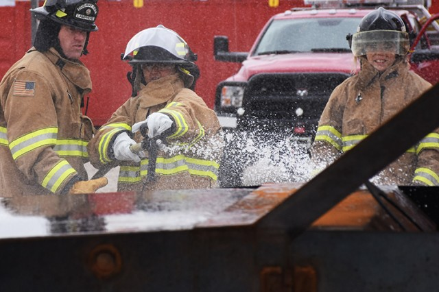 181009-A-BB276-013 Here, Wendy Aoki tries her hand at extinguishing the propane-fired vehicle trainer, coached by Firefighter Branon Lamphere, during the Oct. 9, 2018 Firefighter Skills Day at Dugway Proving Ground, Utah. Right: Deja Galindo watches. Both women are from the Garrison Resource Management office. Photo by Al Vogel, Dugway Proving Ground Public Affairs