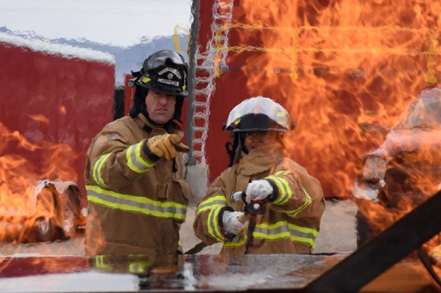 181009-A-BB276-014 Deja Galindo tries her hand at extinguishing the propane-fired vehicle trainer, coached by Firefighter Branon Lamphere, during the Oct. 9, 2018 Firefighter Skills Day at Dugway Proving Ground, Utah. Right: Wendy Aoki watches. Both women are from the Garrison Resource Management office. Photo by Al Vogel, Dugway Proving Ground Public Affairs