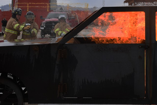 181009-A-BB276-015 Deja Galindo of the Garrison Resource Management office tries her hand at extinguishing the propane-fired vehicle trainer, coached by Firefighter Branon Lamphere, during the Oct. 9, 2018 Firefighter Skills Day at Dugway Proving Ground, Utah. Right: Wendy Aoki watches. Both women are from the Garrison Resource Management office. Photo by Al Vogel, Dugway Proving Ground Public Affairs