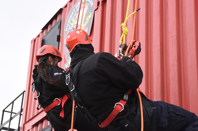 181009-A-BB276-017 Wendy Aoki of the Garrison Resource Management office tries rappelling from a 30-foot tower, coached by a firefighter beside her, during the Oct. 9, 2018 Firefighter Skills Day at Dugway Proving Ground, Utah. The event allowed Dugway employees to try some firefighting skills. Photo by Al Vogel, Dugway Proving Ground Public Affairs