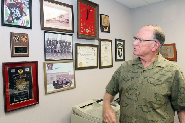 Fort Sill Installation Traffic Manager Ray Jude looks over the photos, awards, and memorabilia he received during his 50-year career in federal service Oct. 18, in his office in Bldg. 4700.