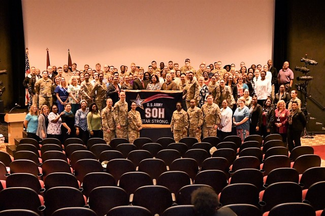 Brig. Gen. Telita Crosland, Regional Health Command-Atlantic commanding general stands with Kenner Army Health Clinic staff with the Army Safety and Occuptional Health Star banner after being presented to the Kenner team during Commander's Call at  Fort Lee Theater, Nov. 8.