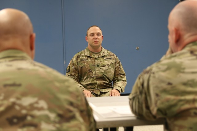 Staff Sgt. Joshua French, Training and Operations, 8th STB, 8th Theater Sustainment Command, sits at attention as he answers questions given to him by the President of the board and all board members.  All questions pertain to the participant's knowledge of soldier's common tasks and leadership skills.