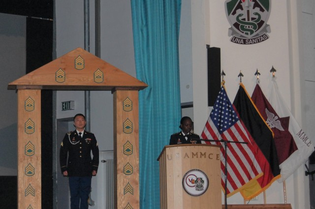 Sgt. Young Kwon, noncommissioned officer in charge of PHCE's Health Physics Division, walks through the NCO arch during the induction ceremony.